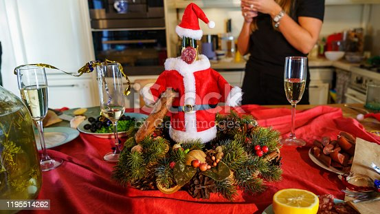 Bottle of Sparking wines in santa claus costume stands on holidy table. New Year and Christmas concept.