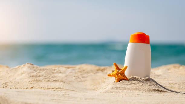 flasche sonnencreme und seesterne am tropischen strand, strand-accessoires und sommer konzept, textfreiraum - salzwasser sandalen stock-fotos und bilder