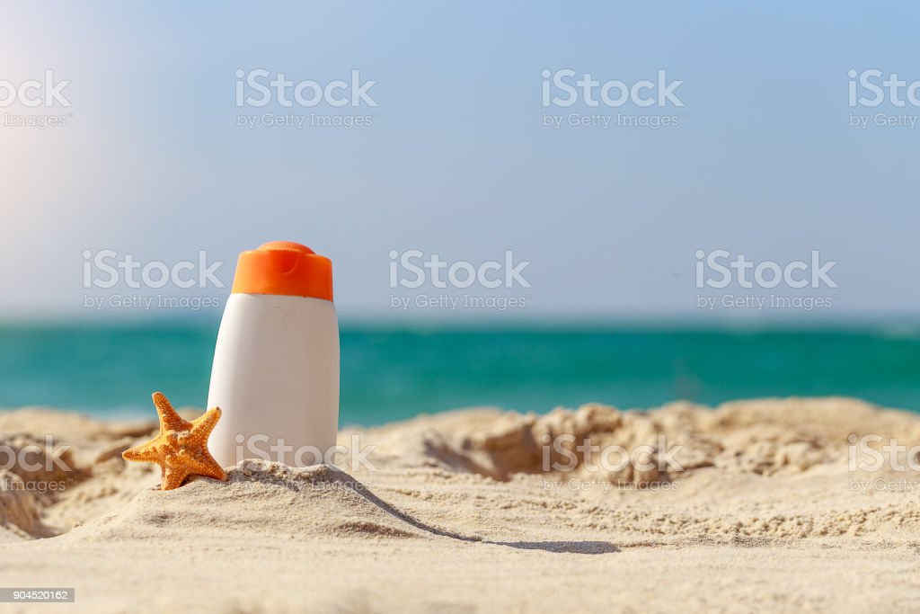 Bottle of sunscreen lotion and starfish on tropical beach, Beach accessories and summer concept, copy space stock photo