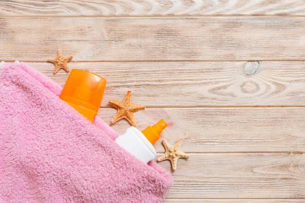 een fles zonnebrandcrème, roze handdoek en schelpen op houten achtergrond. zomerreis concept. bovenaanzicht met kopieerruimte - pink and orange seashell background stockfoto's en -beelden