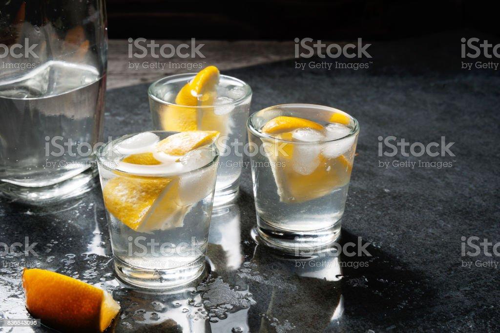 Eine Flasche Wodka oder Gin mit Schnapsgläsern und Zitrone. – Foto