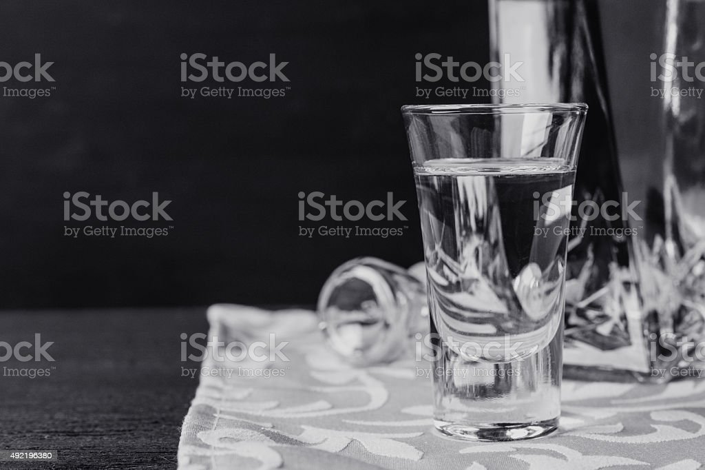 Bottle of vodka with glasses on the wooden table stock photo