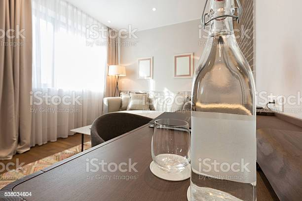 Bottle of water on wooden table in hotel room picture id538034604?b=1&k=6&m=538034604&s=612x612&h=m3xuxborbjdu6luufqkbsirda0pg8r 6a4nc4ps4www=