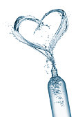 bottle  pouring water that forming a heart shape, isolated on white