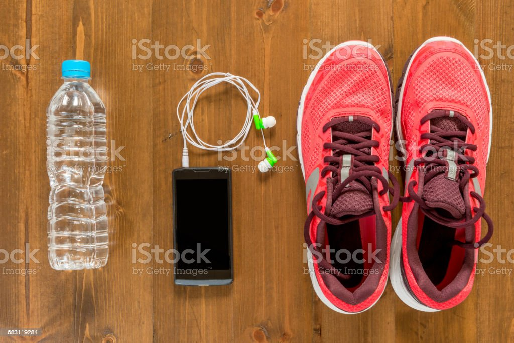 bottle of water, telephone and running shoes for sports on a dark wooden floor view from above close up stock photo