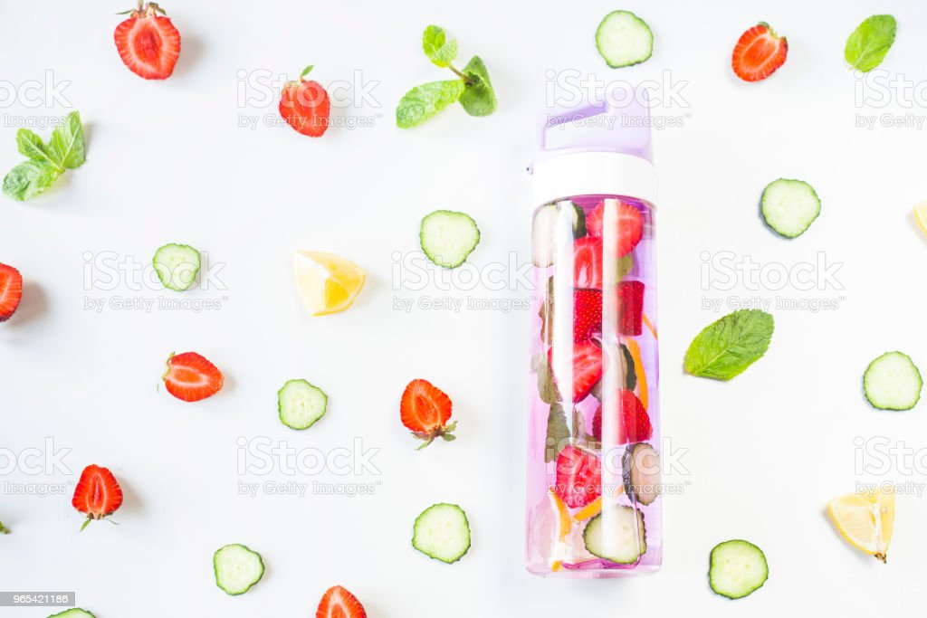 A bottle of water with the addition of strawberries, cucumber, mint and lemon. Among the bright ingredients on a white background. Detox and Sports Concept. Top view, flat lay zbiór zdjęć royalty-free