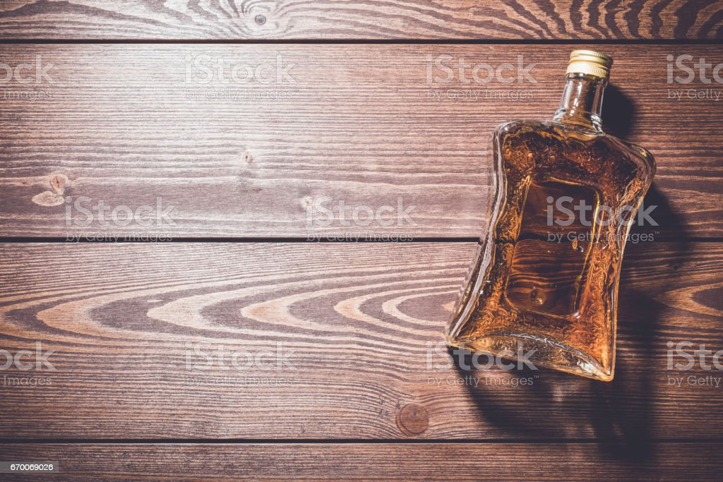 Bottle of whiskey on wooden table stock photo