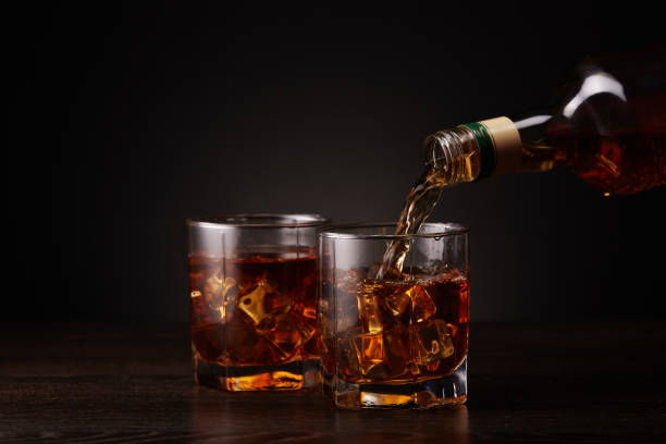 Bottle of whisky and two glasses. Pouring stock photo