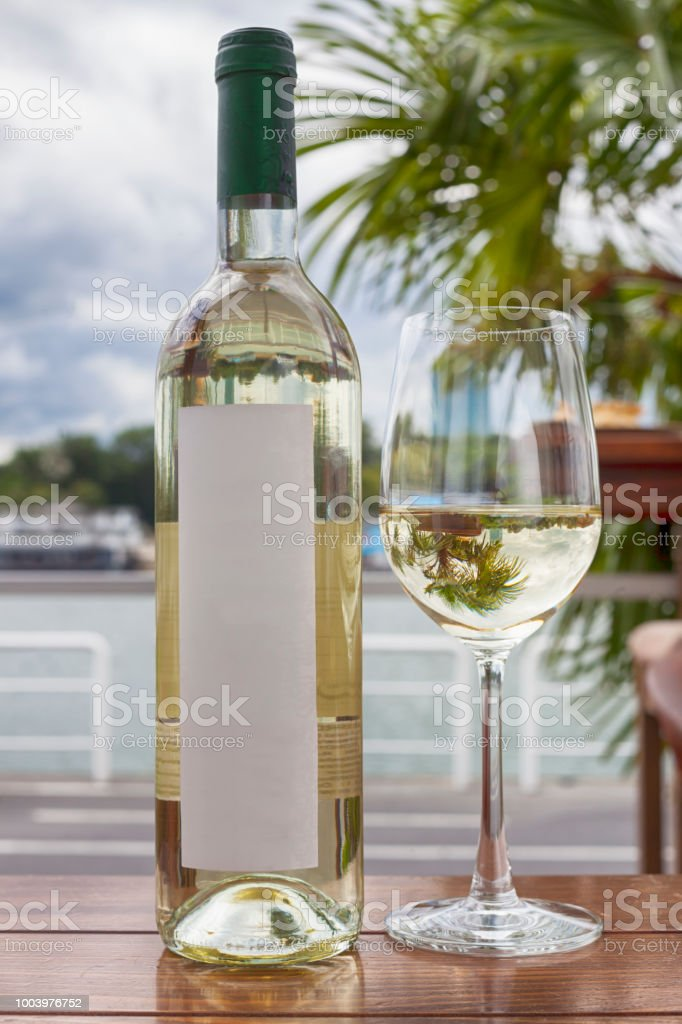 Bottle of white wine and glass by the sea stock photo