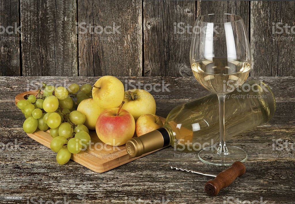 Bottle of white wine, glass and fruits stock photo