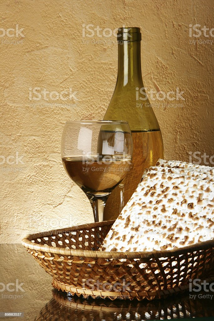A bottle of white wine sets behind a glass and a basket  royalty-free stock photo