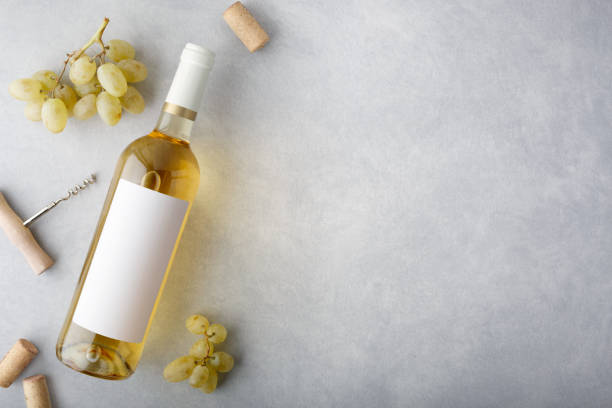A bottle of white wine with a label, grapes, cork and bottle opener. Top view. stock photo