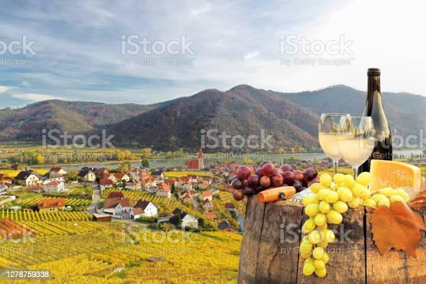 Photo of Bottle of white wine with glasses against Weissenkirchen village with autumn vineyards in Wachau valley, Austria