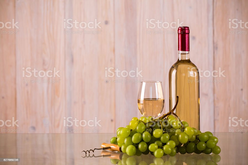 Bottle of white wine with grapes on glass stock photo