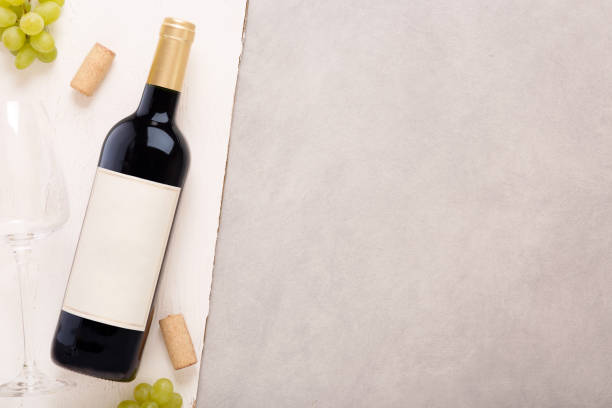 Bottle of white wine with label. Glass of wine and cork. Wine bottle mockup. Top view. stock photo