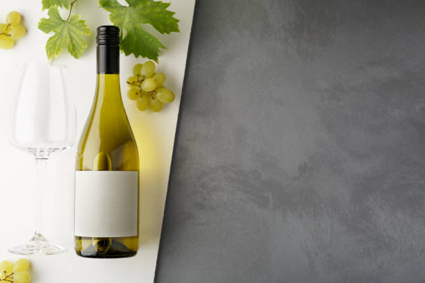 Bottle of white wine with label. Glass of wine and grape. Wine bottle mockup. Top view. stock photo