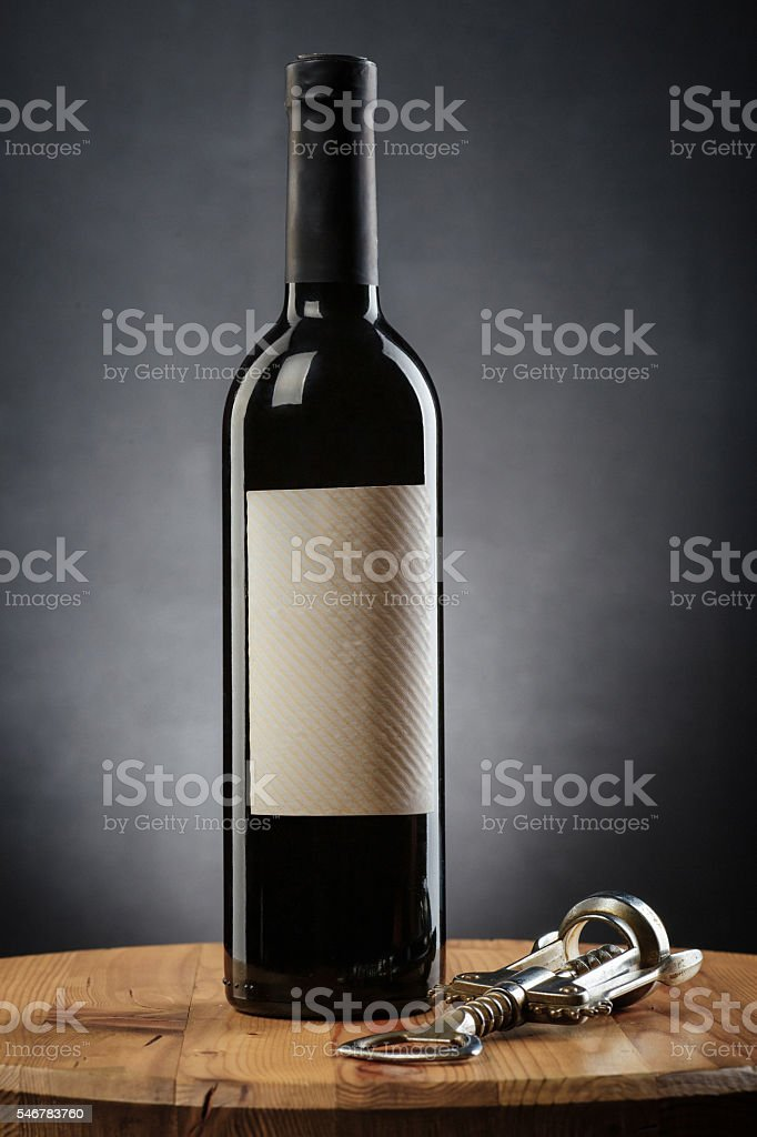 Bottle of wine and corkscrew on wooden table stock photo