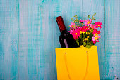 istock bottle of wine and flowers in the package on wooden background, space for text 930600892