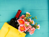 istock bottle of wine and flowers in the package on wooden background, space for text 930601116