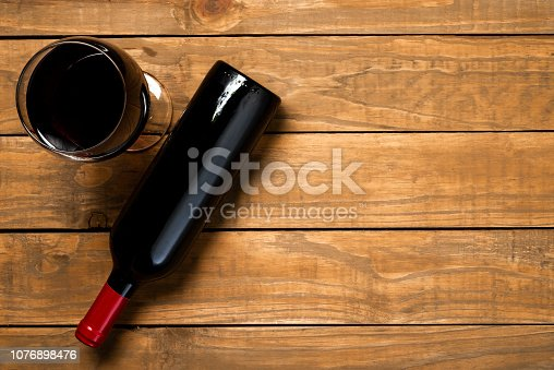 istock Bottle of wine and glass on wooden background. Top view with copy space 1076898476