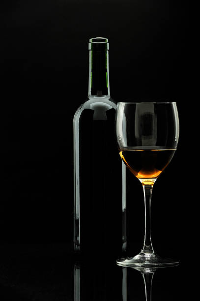 bottle of wine and wineglass over black, stock photo