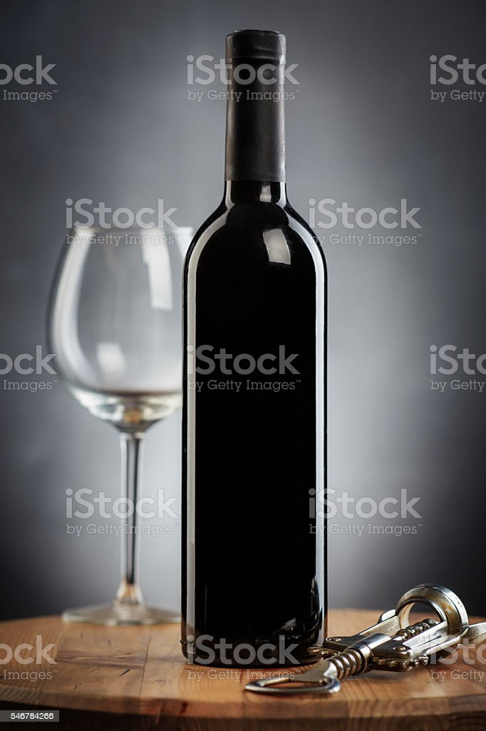 Bottle of wine, glass and corkscrew on a wooden table stock photo