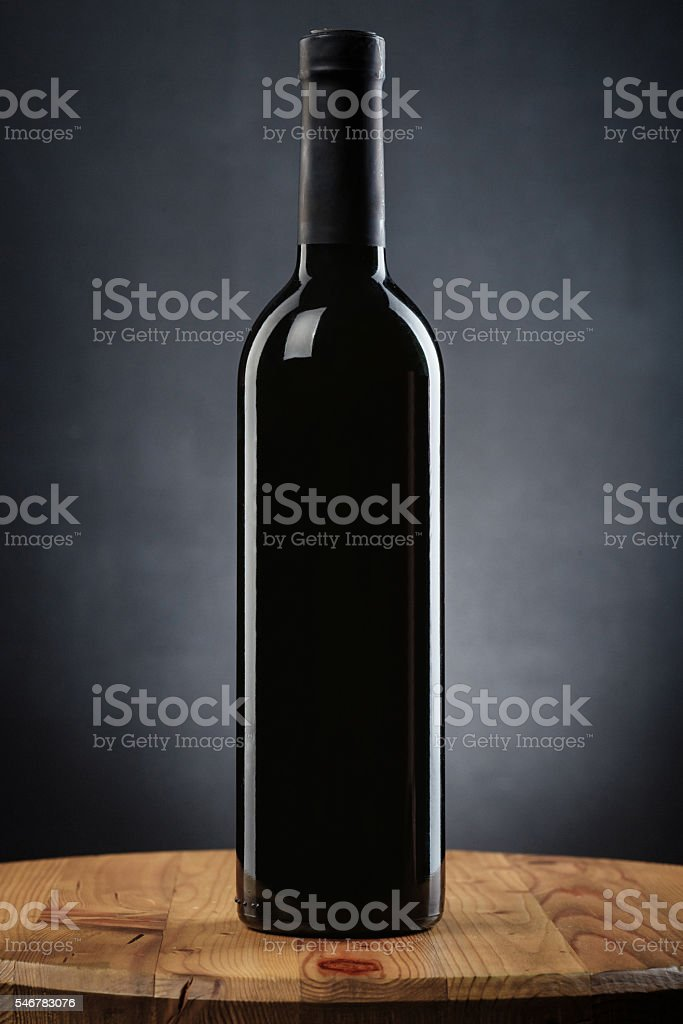 Bottle of wine on a wooden table on gray background stock photo