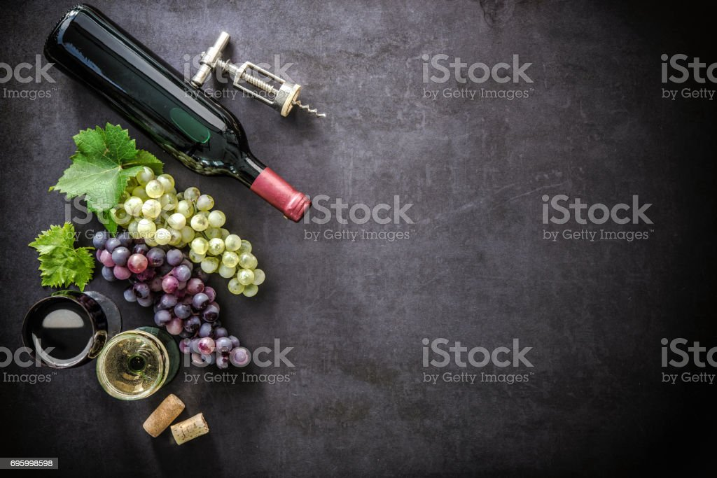 Bottle of wine, wineglasses, grapes and corks stock photo