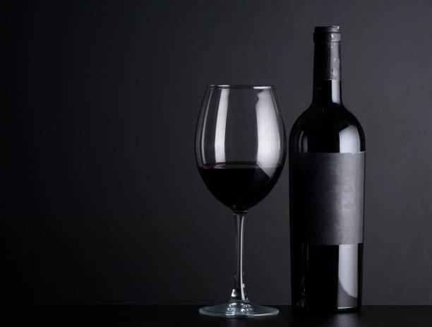 bottle of wine with a glass on a black background stock photo