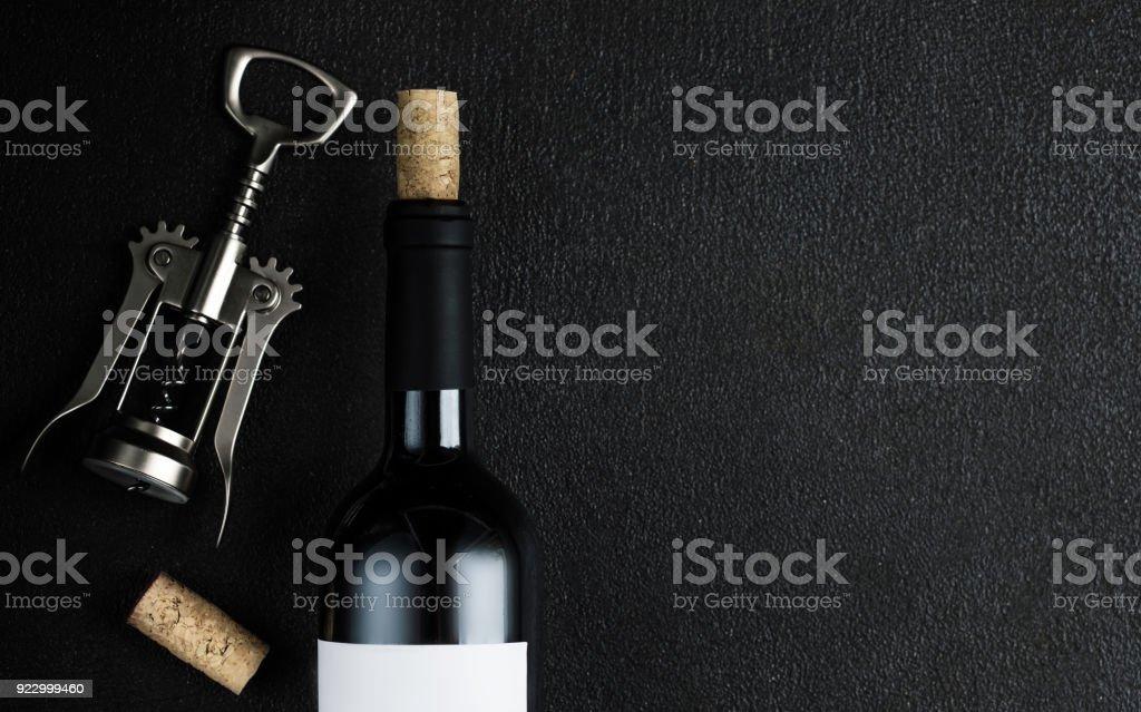 Bottle of wine with corkscrew on the black stone background, Wine degustation concept stock photo