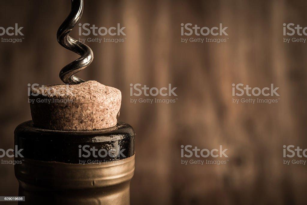 Eine Flasche Wein mit Korkenzieher auf hölzernen Hintergrund  – Foto
