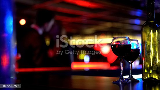 istock Bottle of wine with two glasses, kissing young couple on blurred background 1072207512