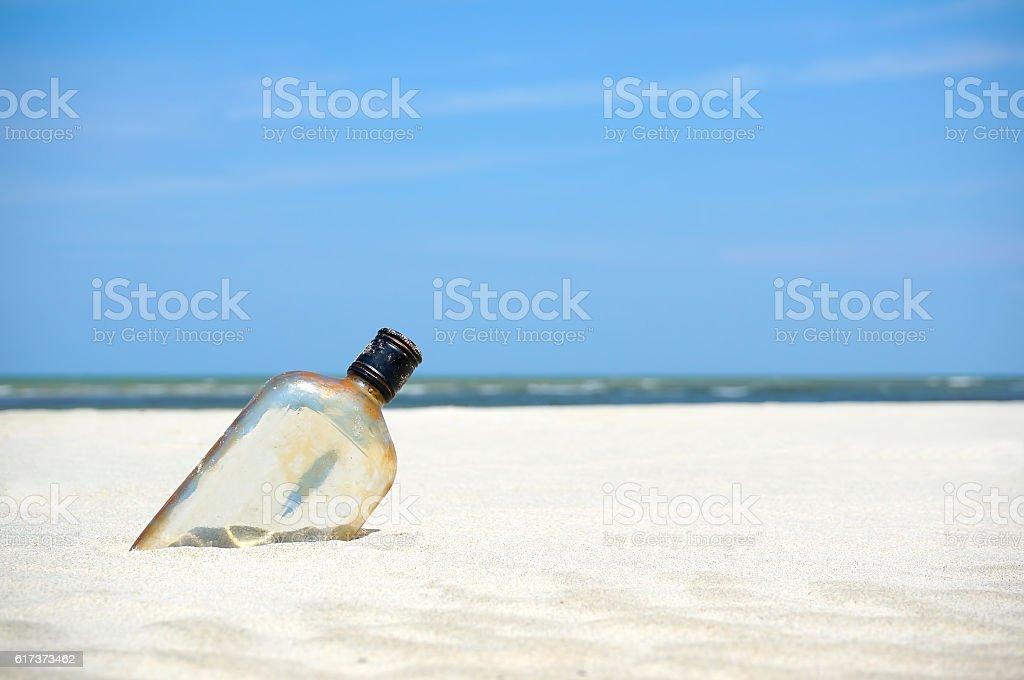 Bottle on a sand beach stock photo