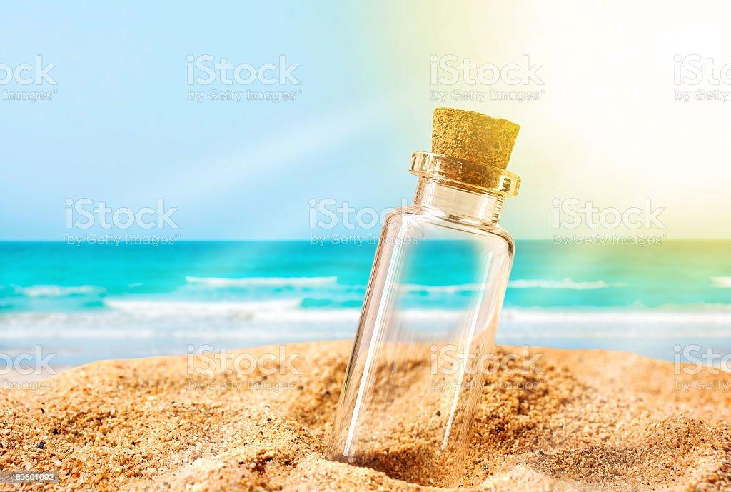 Bouteille sur une plage de sable et de soleil ray. - Photo