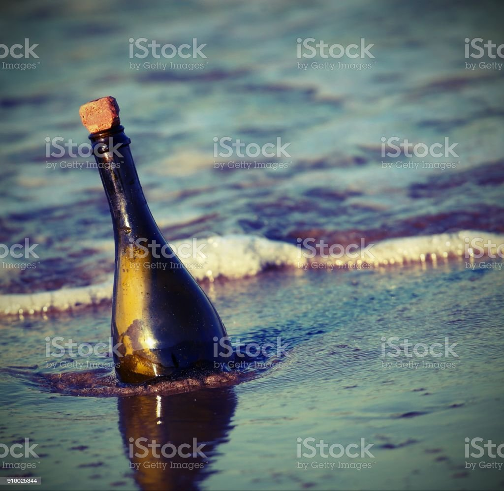 bottle on the beach with a secret message stock photo