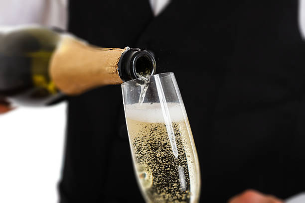 Bottle pouring champagne into flute stock photo