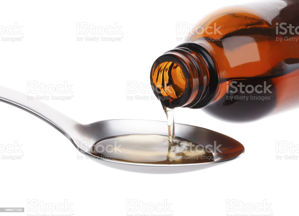 Bottle pouring Medicine Syrup in Spoon stock photo
