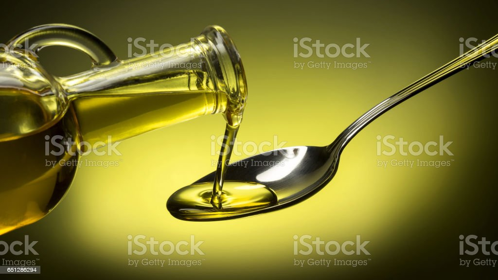 bottle pouring oil in a spoon on green background stock photo