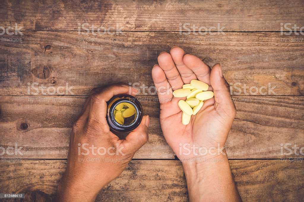 bottle pouring pills on a male's hand stock photo