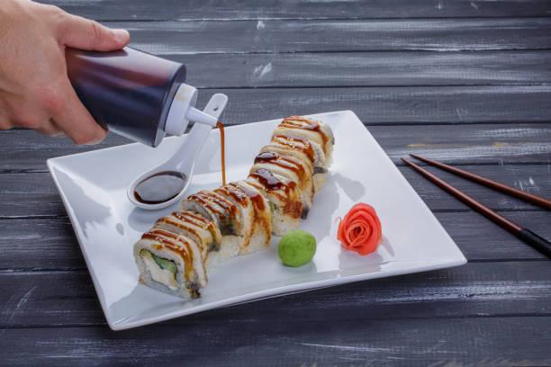 garrafa derramando molho para sushi. squeeze garrafa na mão do homem. japão envia saudações. uramaki rolos de sushi café. - squeeze bottle - fotografias e filmes do acervo