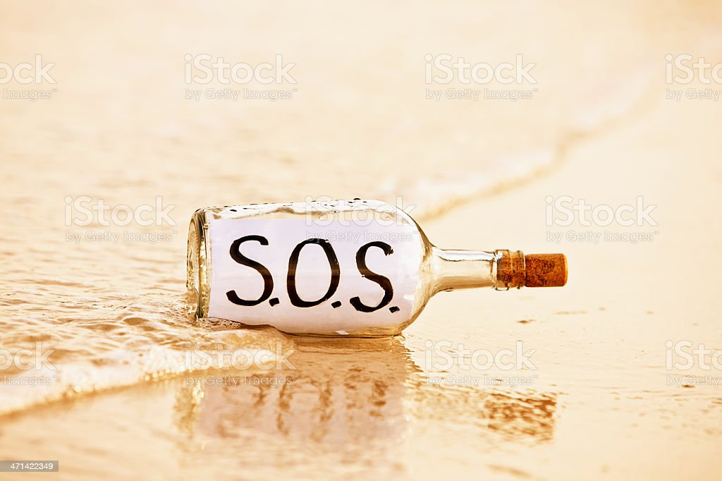Bottle washing up in surf on shoreline contains SOS message stock photo