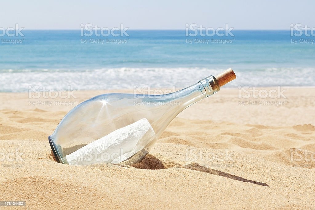 Bottle with a letter of distress on the beach. stock photo
