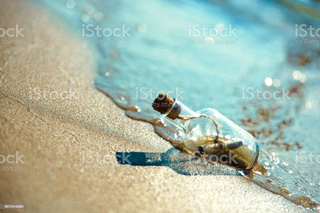 Une bouteille avec un message est levée par une vague sur une plage de sable fin. Fond de sable. Le flacon flotte dans la ligne de surf - Photo