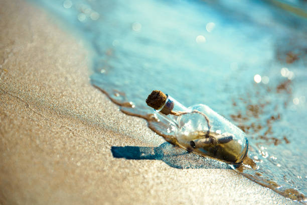 une bouteille avec un message est levée par une vague sur une plage de sable fin. fond de sable. le flacon flotte dans la ligne de surf - message écrit et lettre de photos et images de collection