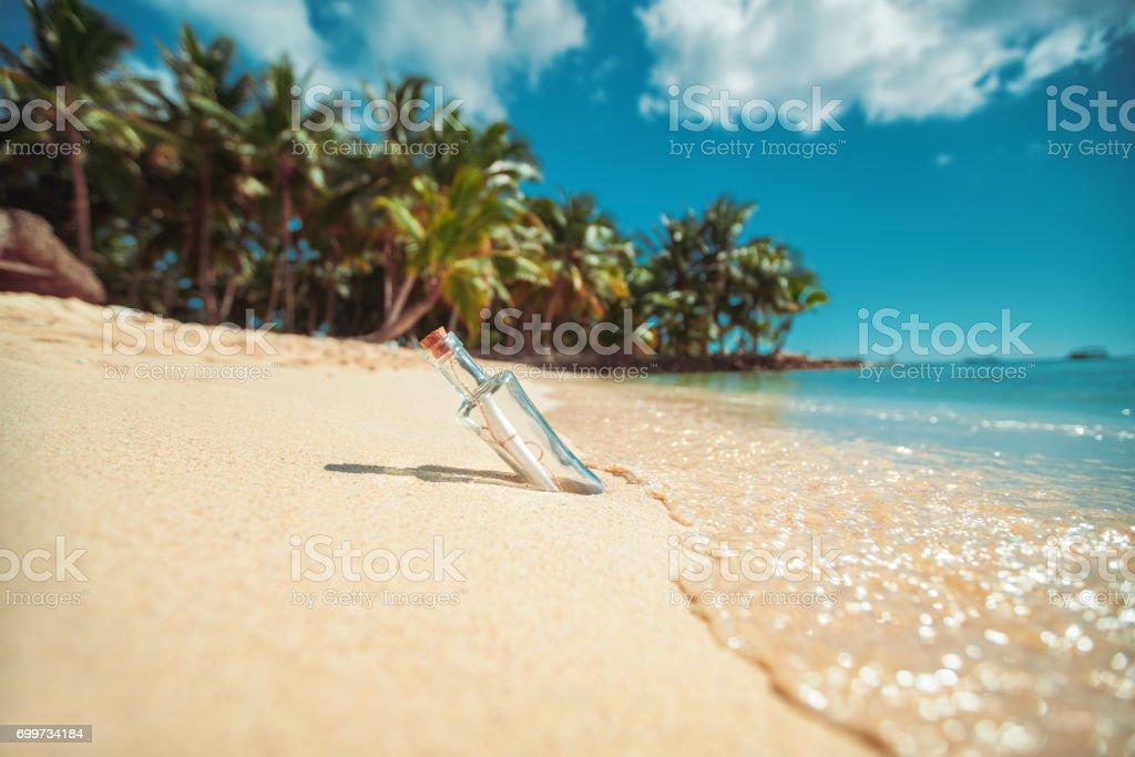 Bouteille avec un message sur une plage de l'île tropicale - Photo