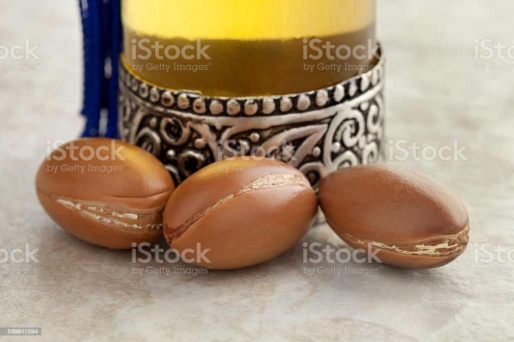 Bottle with argan oil and nuts stock photo