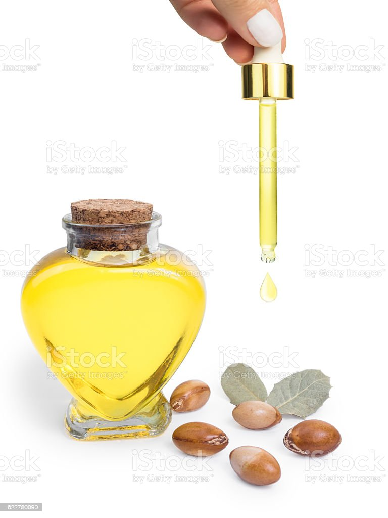 Bottle with argan oil. Cosmetic means. Food product. Isolated background. - foto de stock