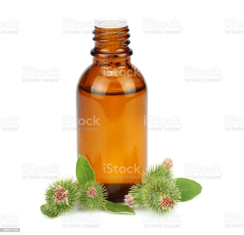 bottle with burdock (castor, agrimony) oil isolated on white background stock photo