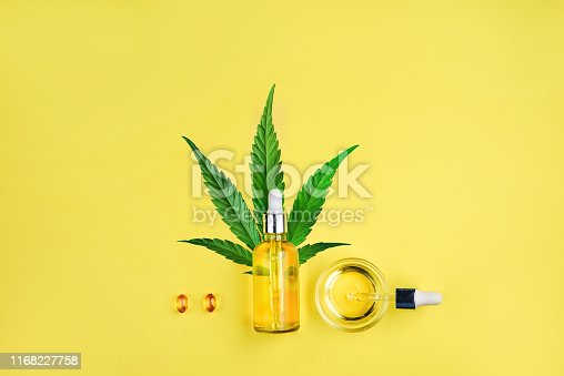 istock Bottle with CBD oil, pipette, capsules and cannabis leaf on a yellow background. Minimalism, flat lay. 1168227758
