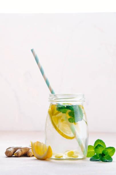 flasche mit entgiftungswasser mit zitrone, ingwer und minze - ingwerwasser zubereiten stock-fotos und bilder